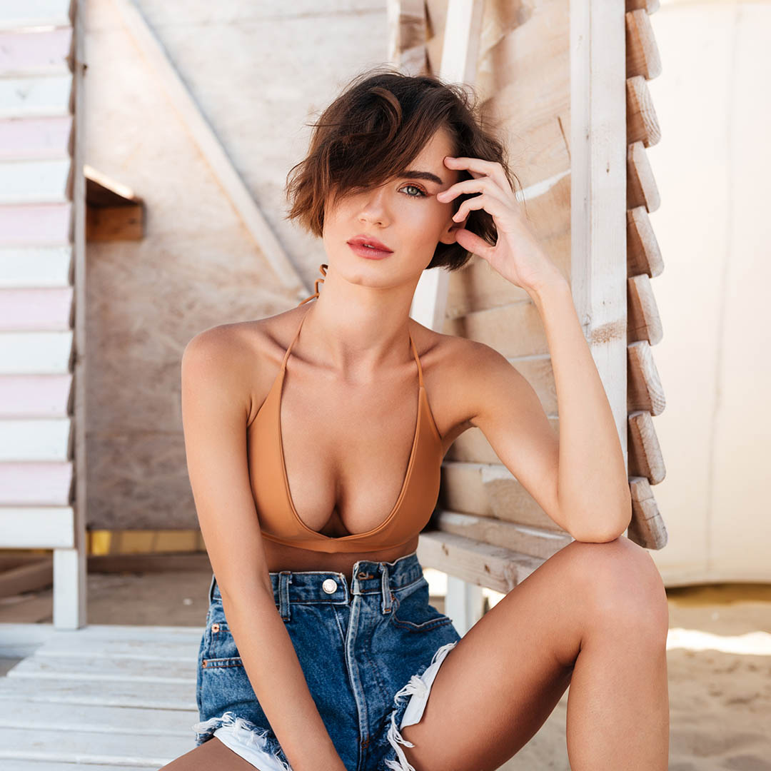 Young thoughtful lady in bikini and denim shorts sitting on wood floor with locker room on background on the beach. Portrait of beautiful girl dreamily posing and looking in camera