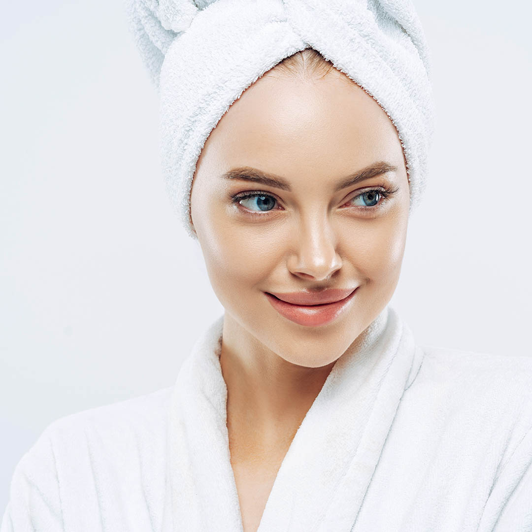 Day spa, beauty and freshness concept. Pensive European woman with healthy skin concentrated aside thoughtfully, feels refreshed after bath procedures, dressed in dressing gown, towel on head